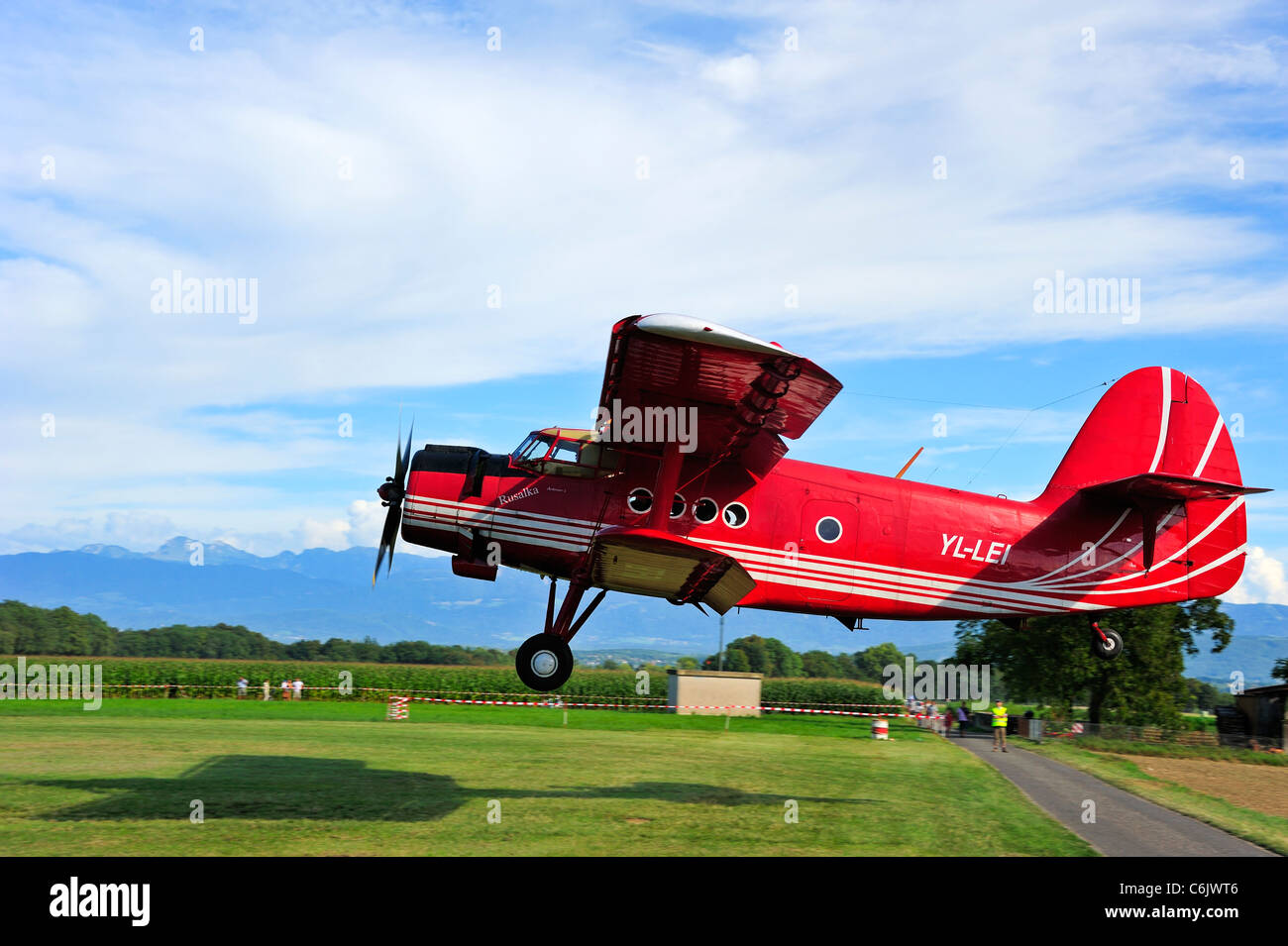 An Antonov AN-2 biplane landing. Motion blur on the background. Space for text in the sky. - Stock Image