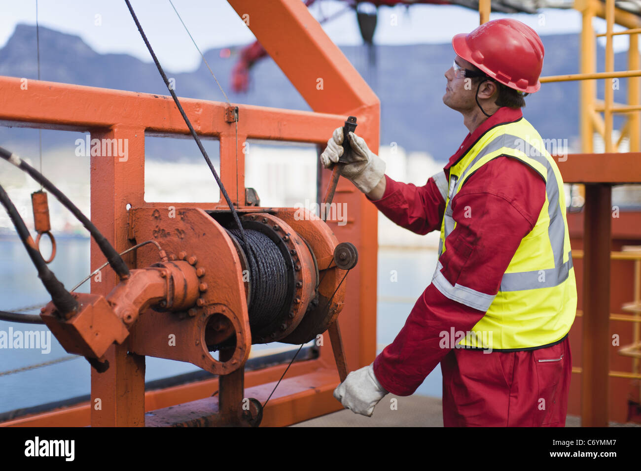 Worker spooling cord on oil rig - Stock Image