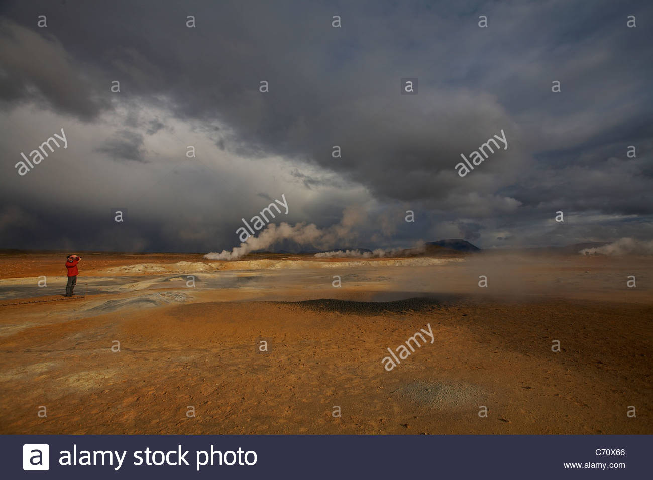 Man examining steam of geothermal rivers - Stock Image