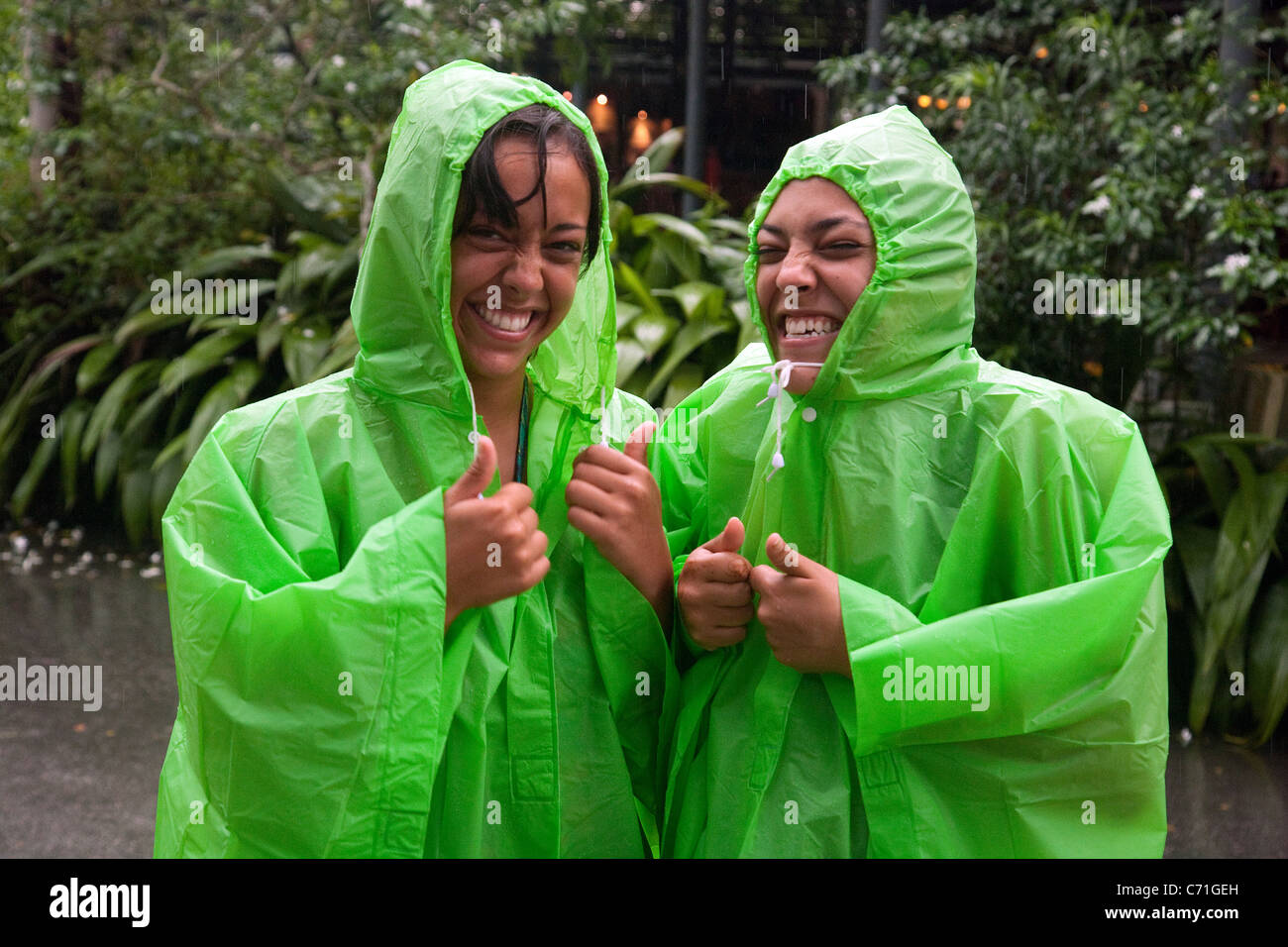 two-teenage-indian-girls-laughing-and-having-fun-in-the-rain-singapore-C71GEH.jpg