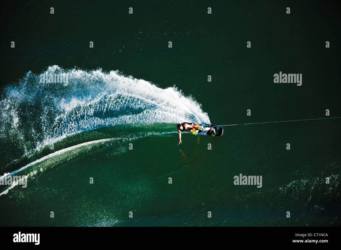 A athletic wakeboarder carves and slashes on a calm day in Idaho. Shot from above. - Stock Image