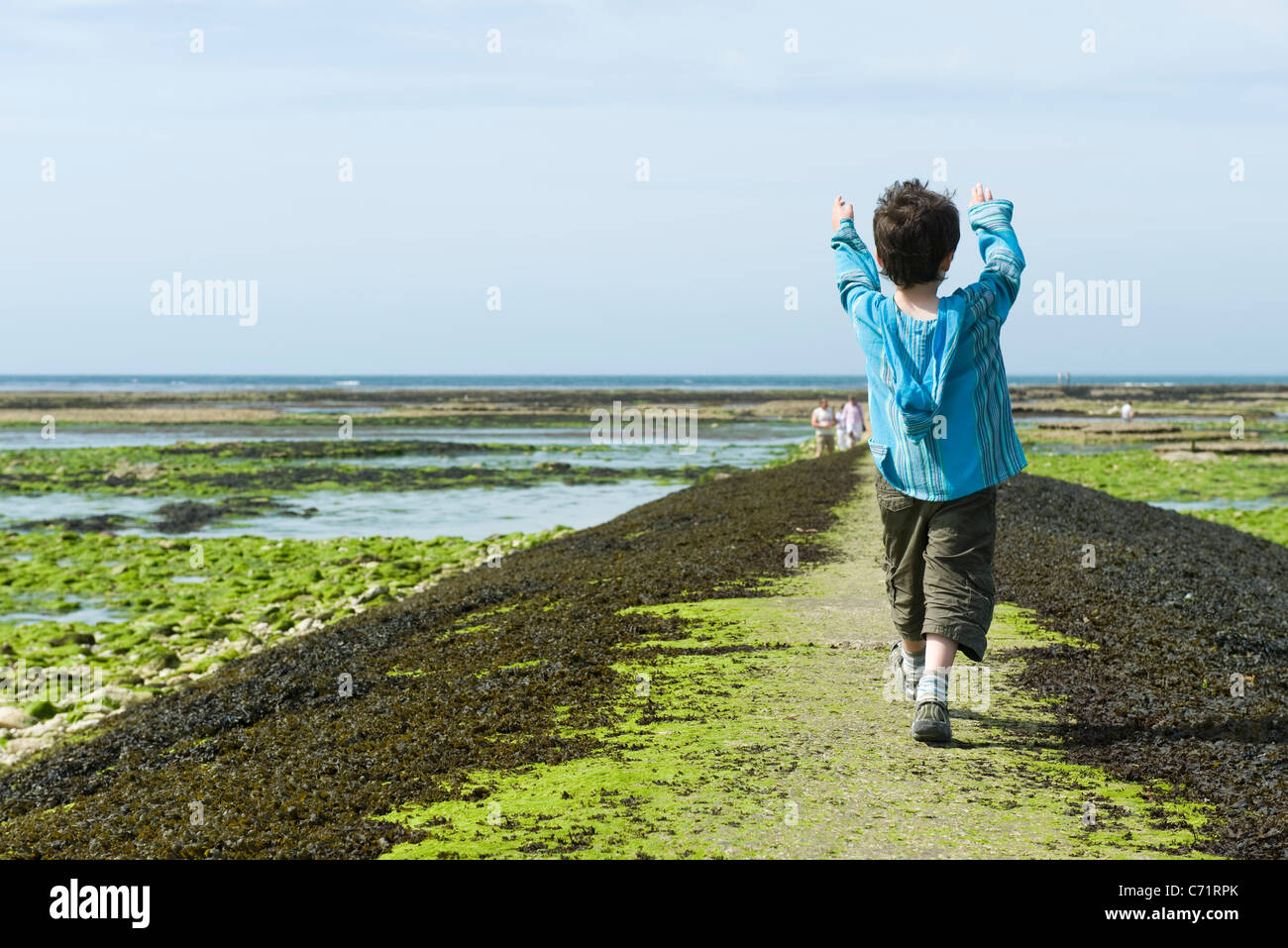 Boy walking on breakwater, Ile de RŽ, Charente-Maritime, France - Stock Image