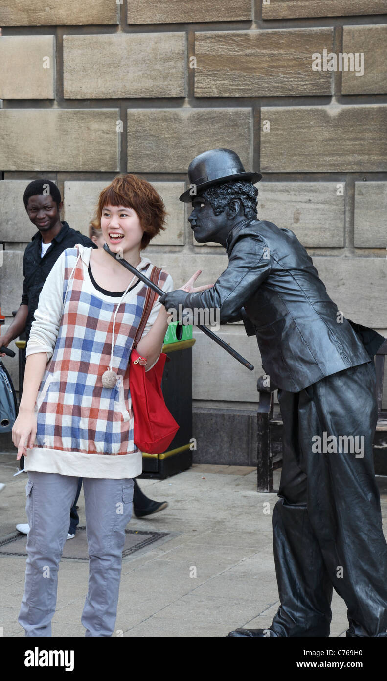 chaplinesque-street-performer-interacting-with-member-of-audience-C769H0.jpg