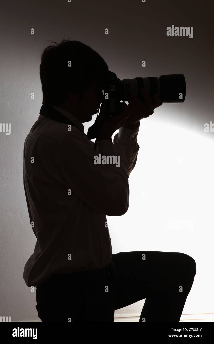 Silhouette of a photographer. - Stock Image