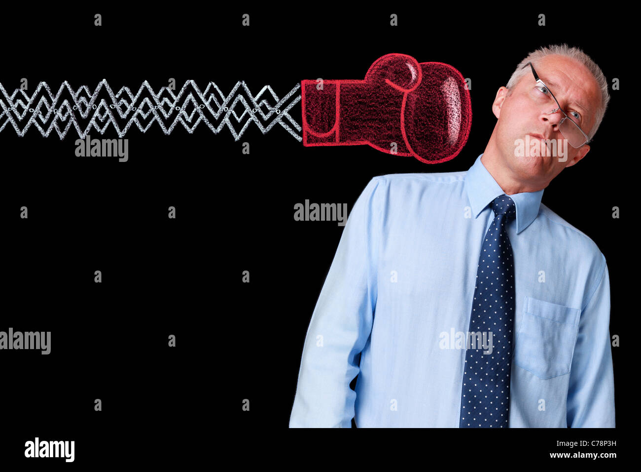 Photo of a mature businessman against a black background being delivered a knockout punch by a handrawn chalk boxing - Stock Image