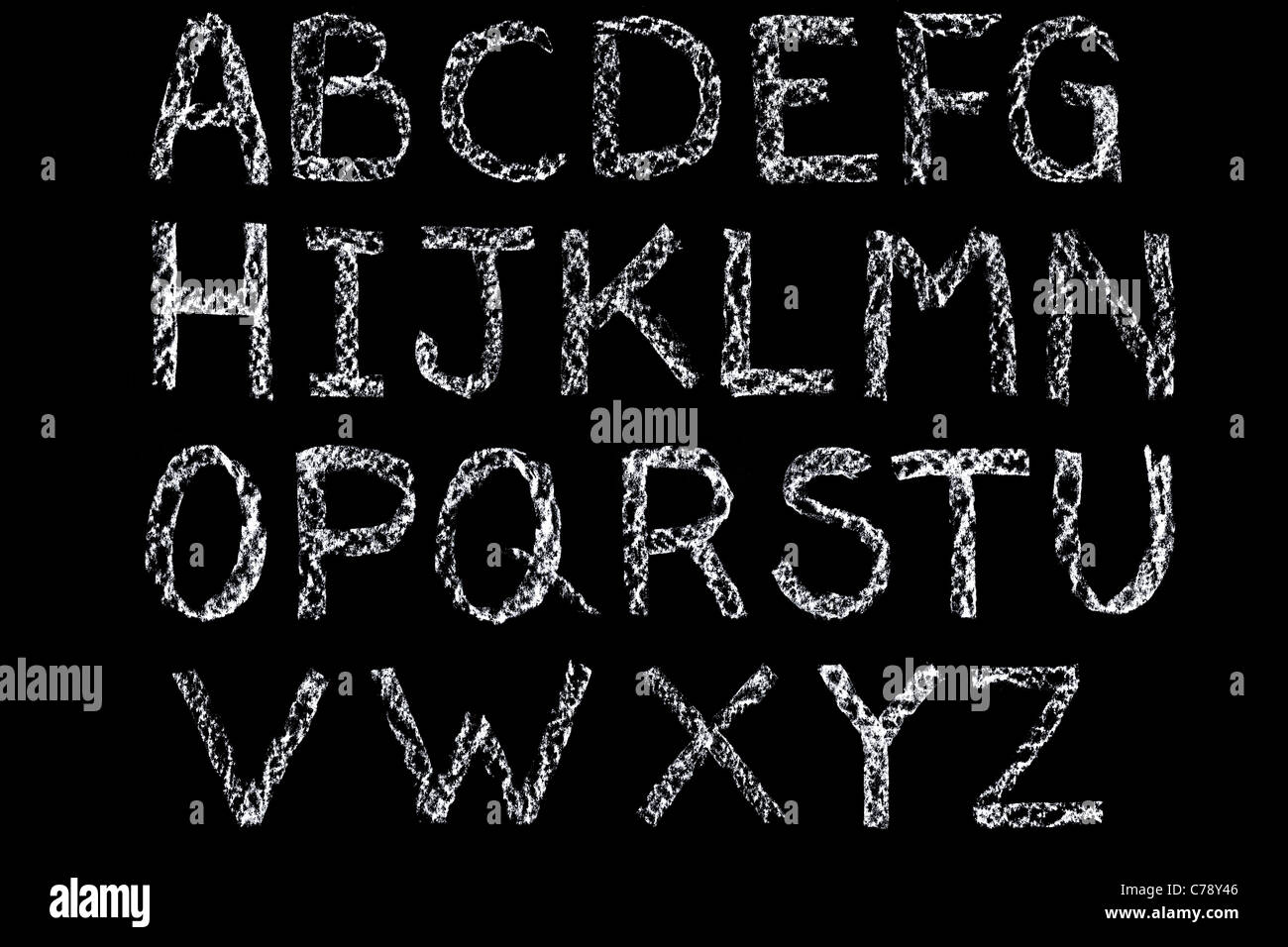 Handwritten letters of the alphabet written on a blackboard in white chalk then cleaned up during editing - Stock Image
