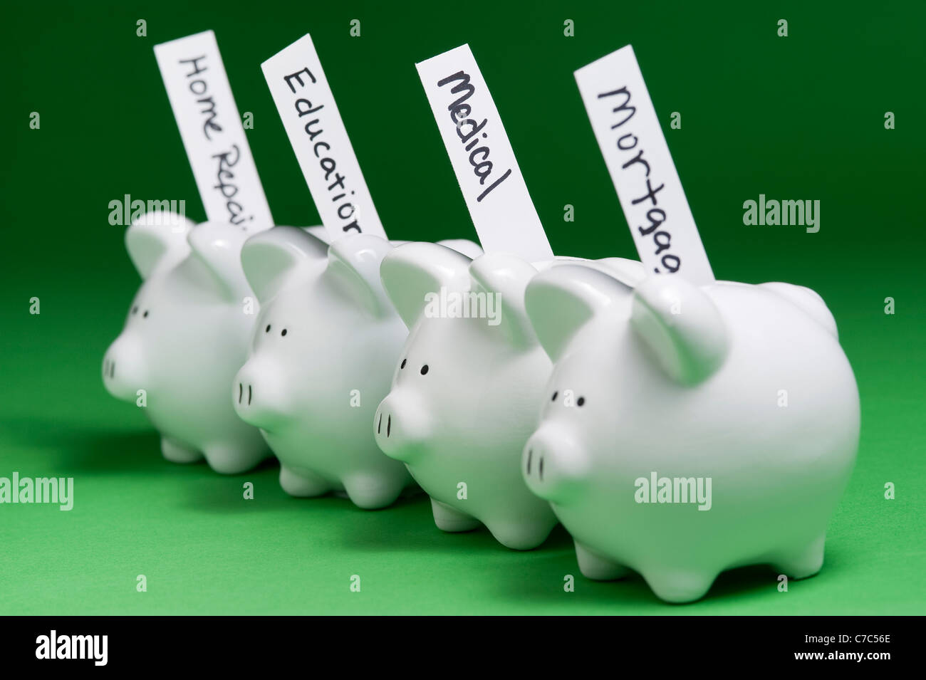 Piggy banks with bills coming out of coin slots with pigs lined up in a row - Stock Image