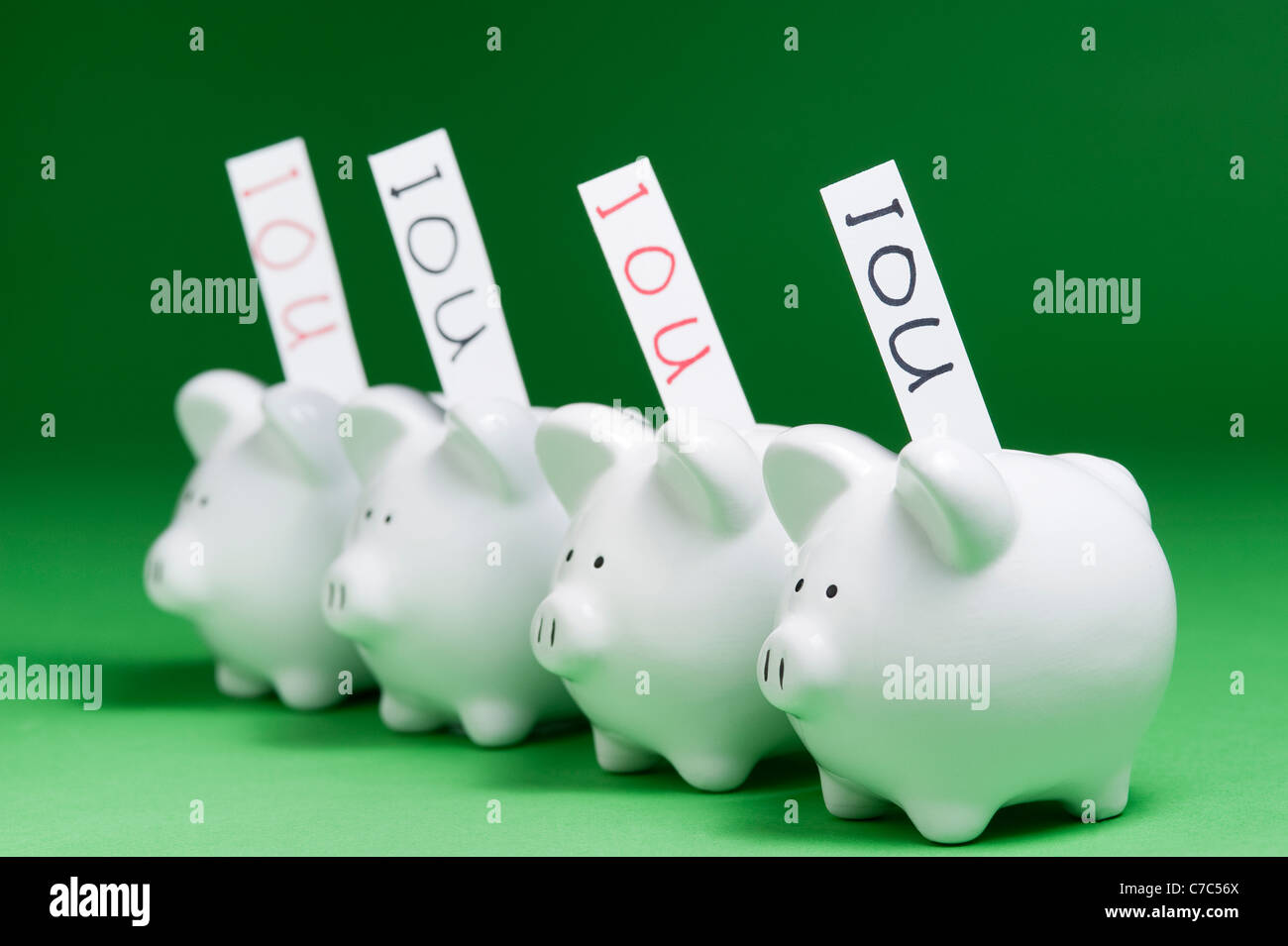 Group of piggy banks with IOU's coming out of coin slots - Stock Image