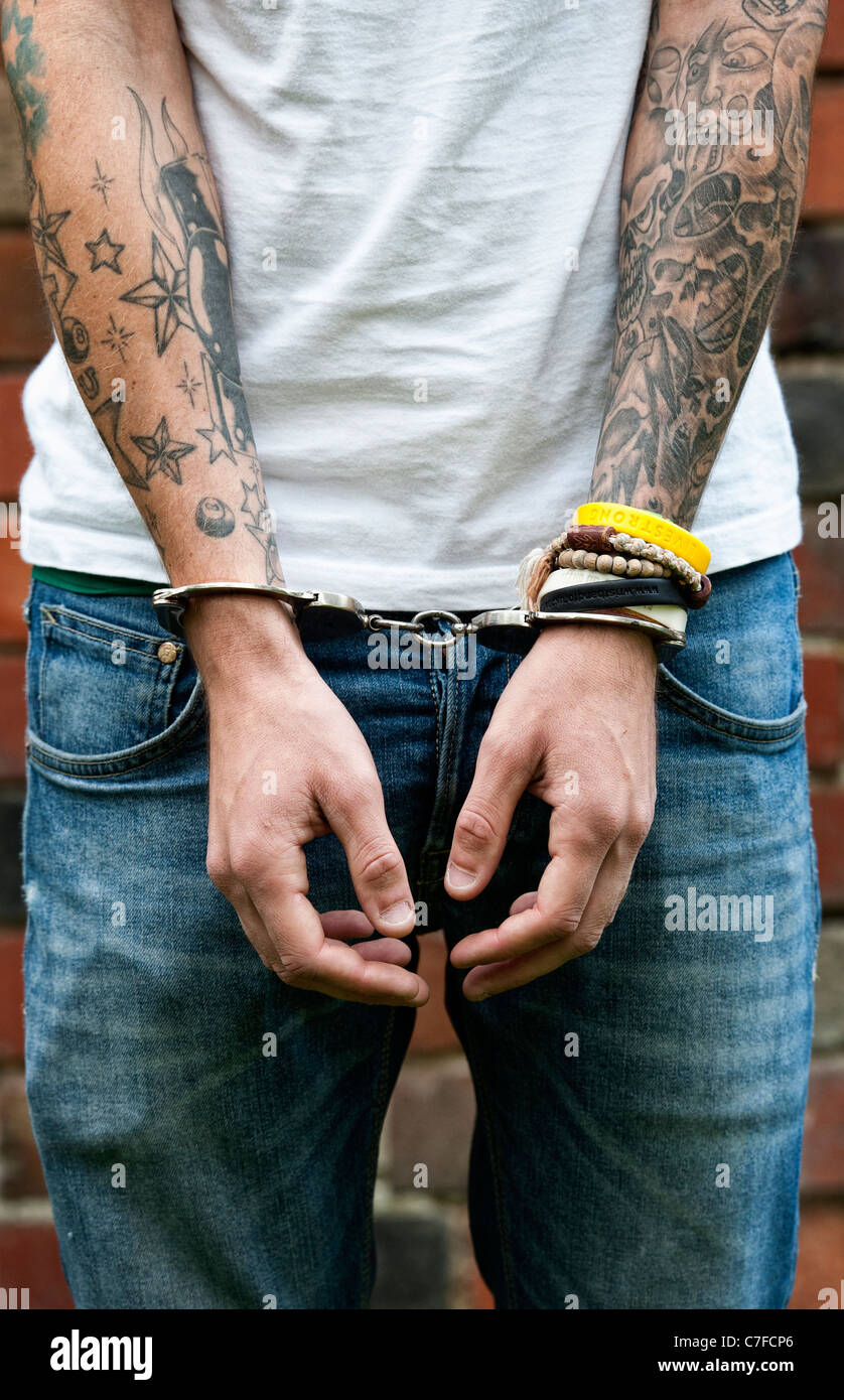 Handcuffed teenager with tattoos - Stock Image