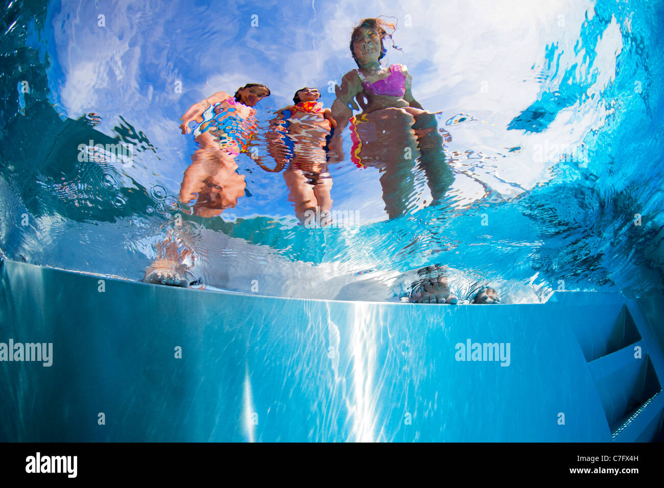 Children on the side of an open air swimming pool (Bellerive-sur-Allier - France). Underwater view. - Stock Image