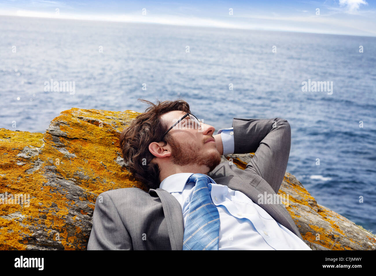 Businessman relaxing on cliff - Stock Image