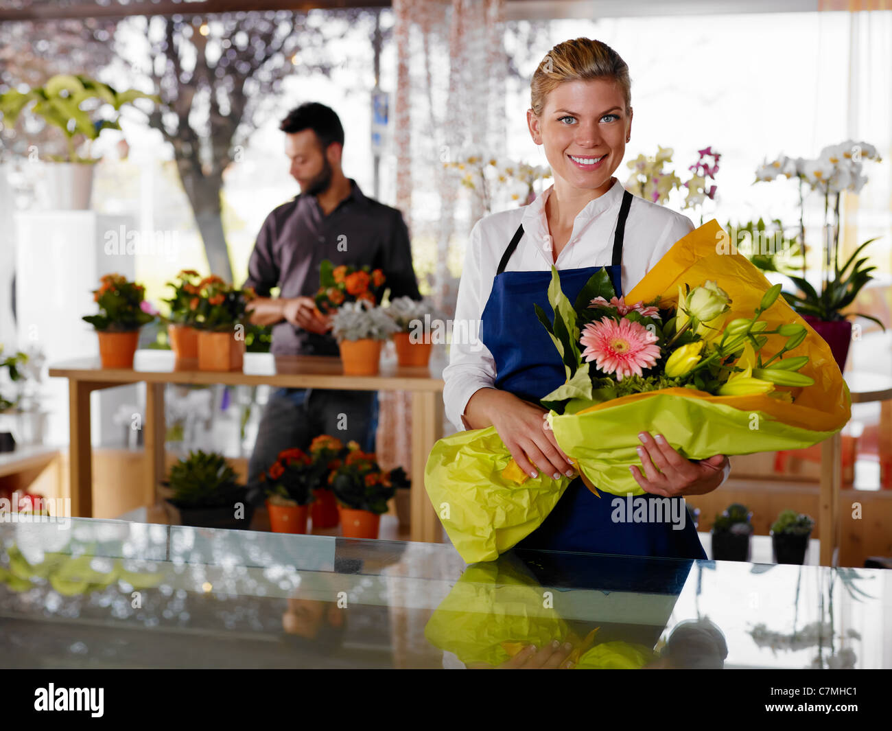Female sales assistant working as florist and holding bouquet with customer in background. Horizontal shape, waist - Stock Image