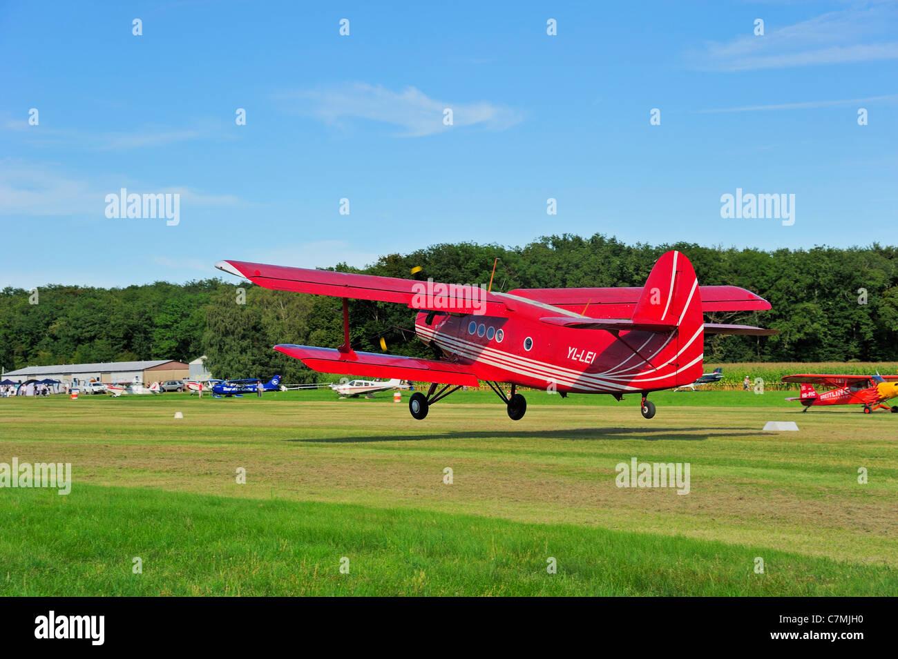 An Antonov AN-2 biplane landing on a grass airstrip. - Stock Image