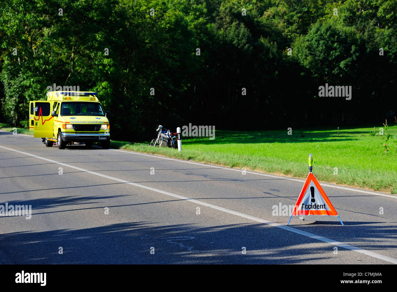 Swiss ambulance at the site of an accident. Focus on the accident sign. The accident involved a cyclist hit by a - Stock Image