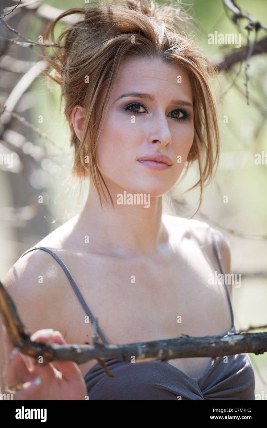 Portrait of young beautiful auburn haired woman in the forest, standing among bare tree branches. Stock Photo