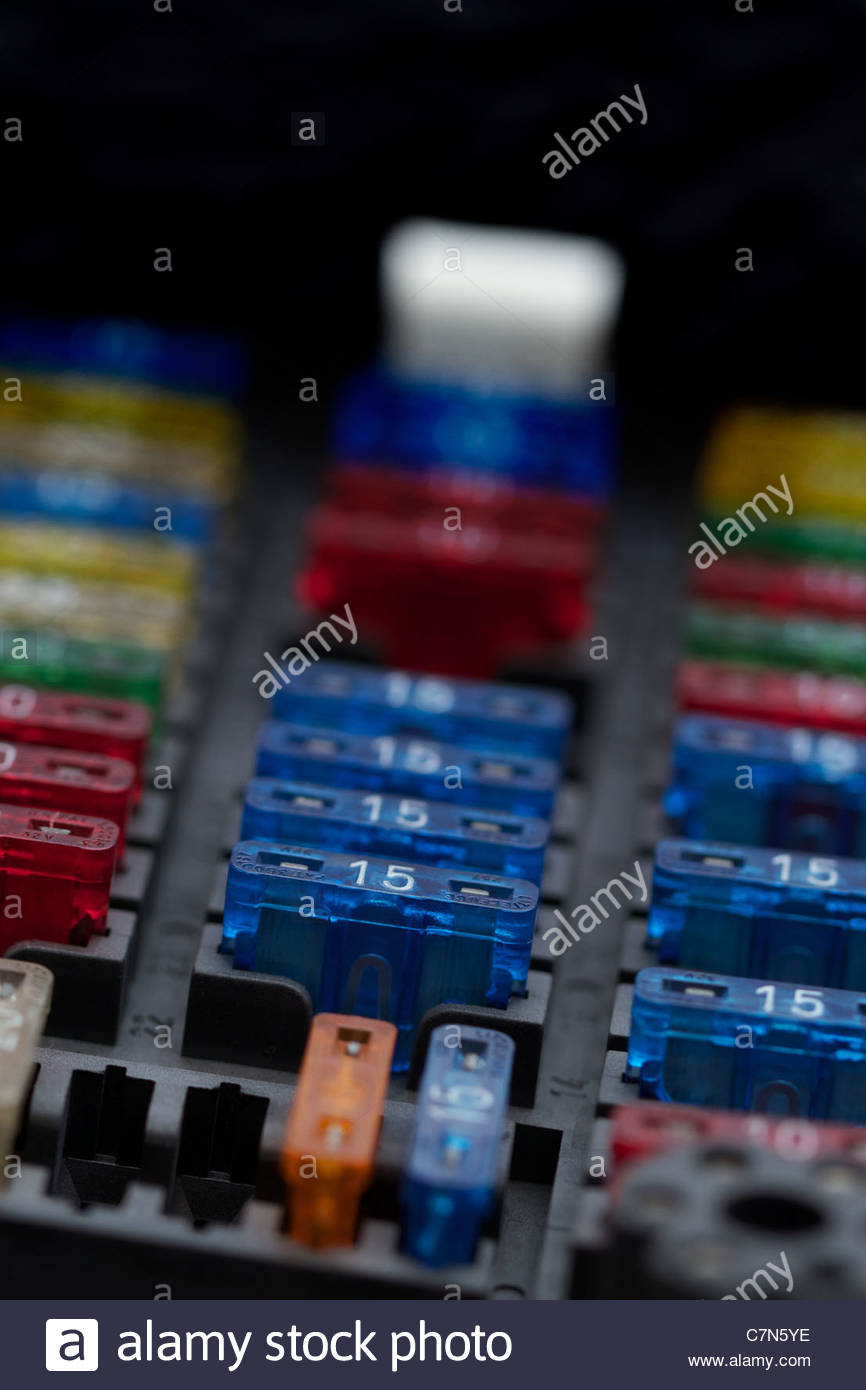 Different regular size blade type fuses in car fuse box. Shallow depth of field. - Stock Image