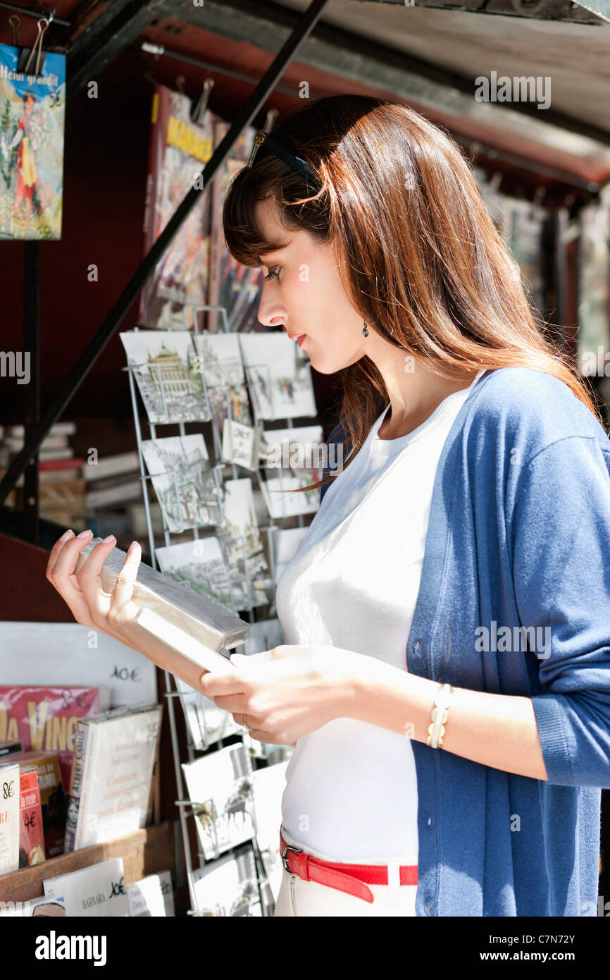 Woman reading a book at a book stall, Paris, Ile-de-France, France - Stock Image