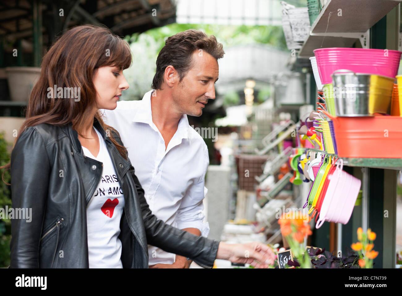 Couple shopping at a market stall, Paris, Ile-de-France, France - Stock Image