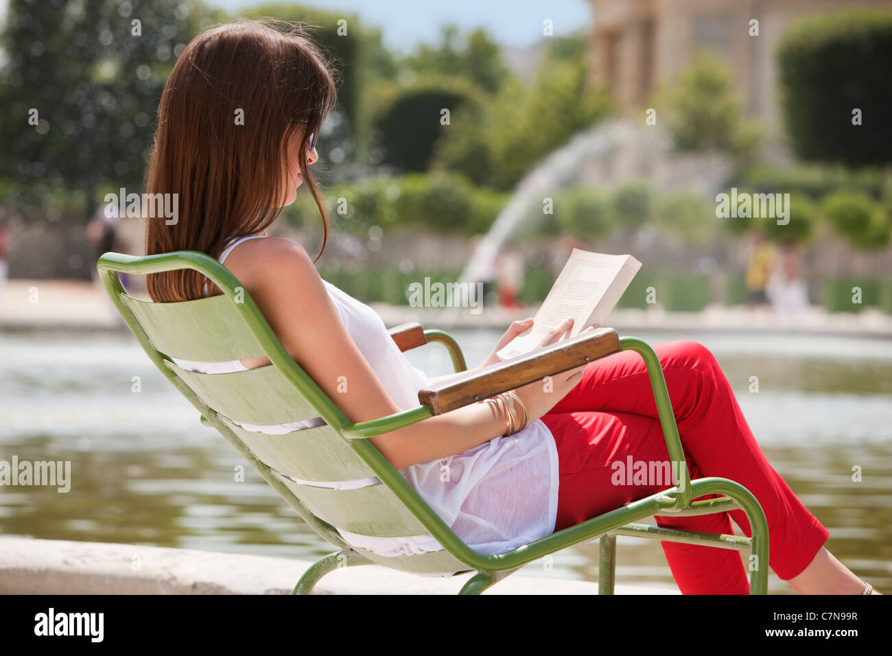 Woman reading a magazine, Jardin des Tuileries, Paris, Ile-de-France, France - Stock Image