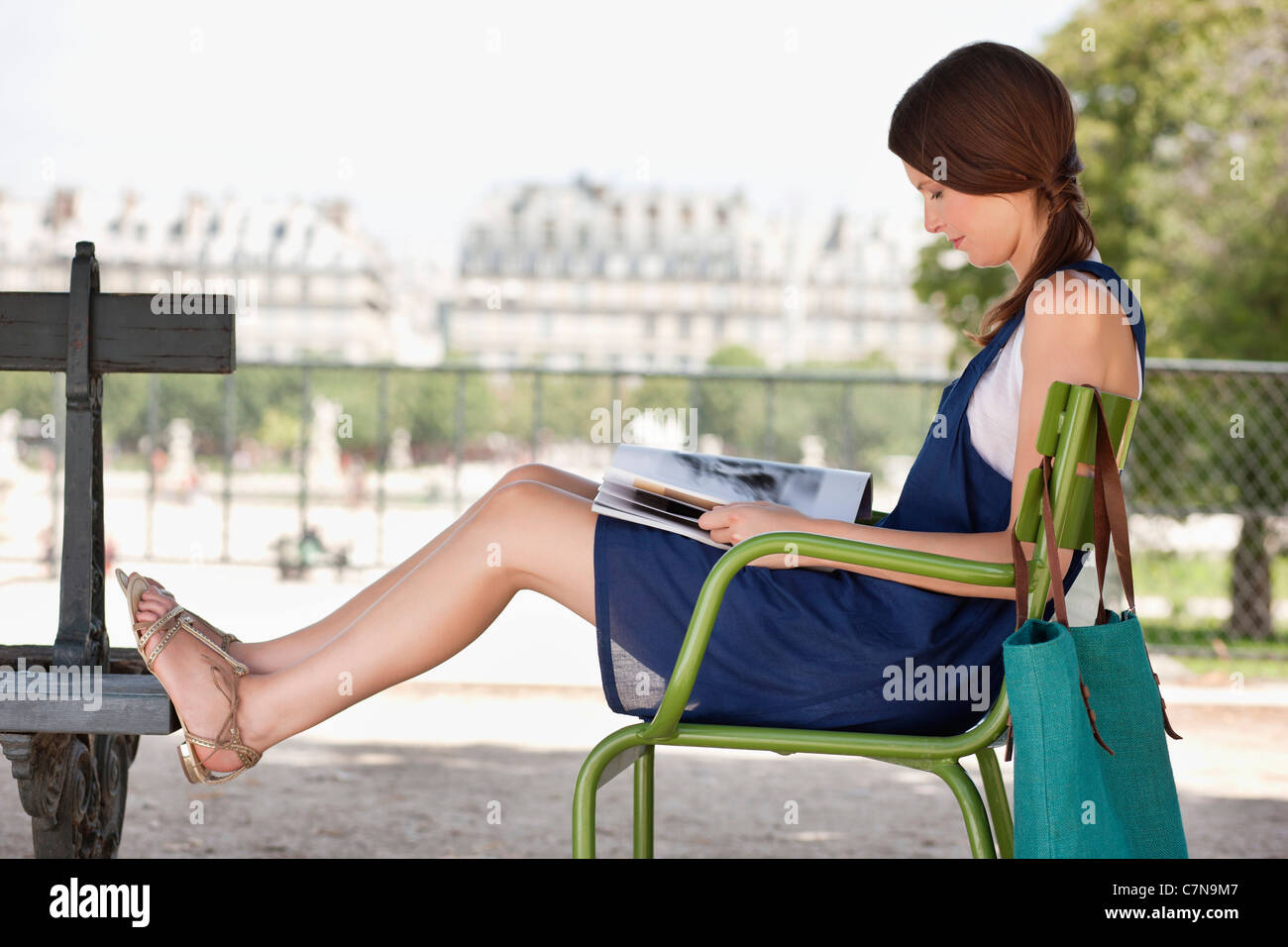 Woman sitting in a chair and reading a magazine, Jardin des Tuileries, Paris, Ile-de-France, France - Stock Image