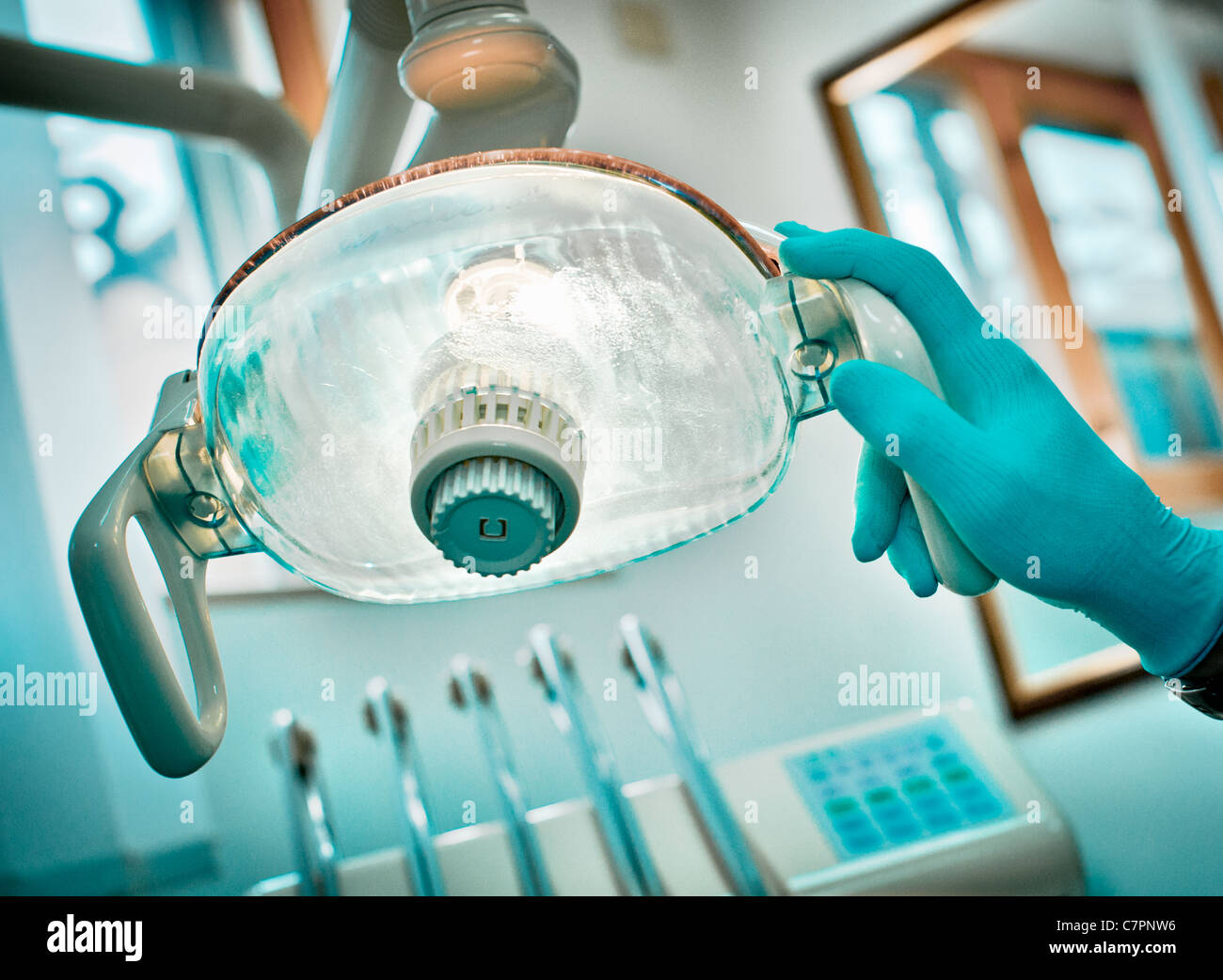 Dentist adjusting lamp in office - Stock Image