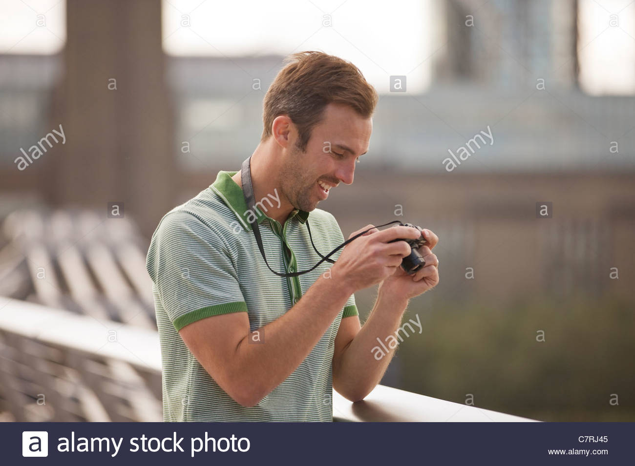A mid-adult man looking at his photographs on his camera - Stock Image
