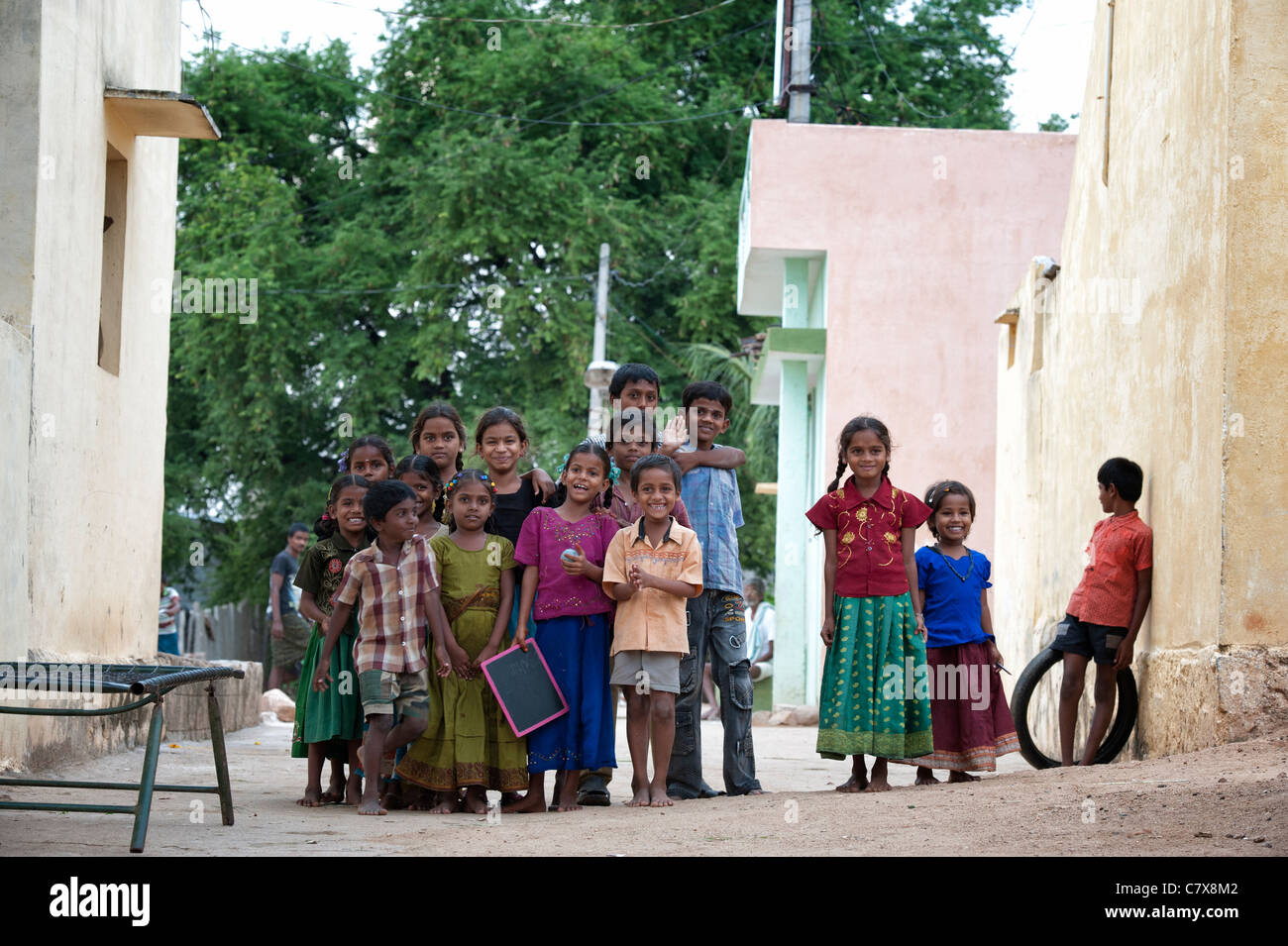 Happy young rural Indian village children smiling in the street. Andhra Pradesh, India - Stock Image
