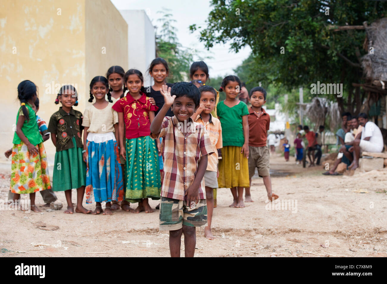 Happy young rural Indian village boy laughing waving in front of a group of  village children. Andhra Pradesh, India. - Stock Image