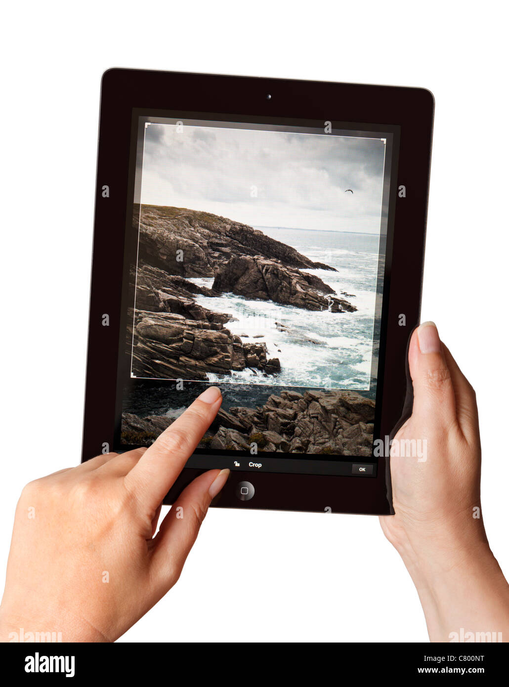Hands holding an iPad2 using a Photoshop app to edit a photo - Stock Image
