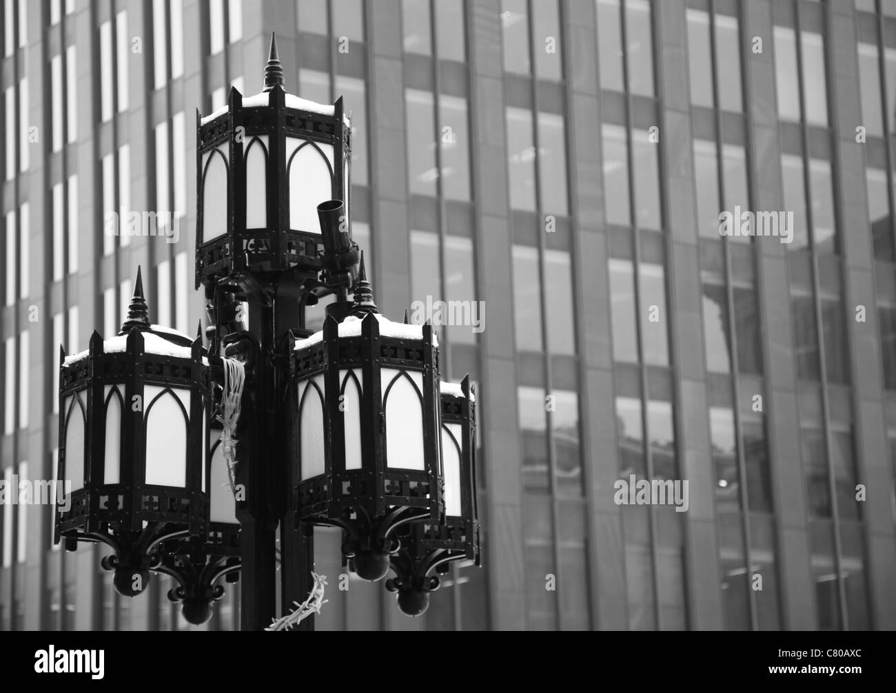 black and white photograph of a iron lamp post in historic downtown Montreal, Quebec, Canada, sky scrapper in the - Stock Image
