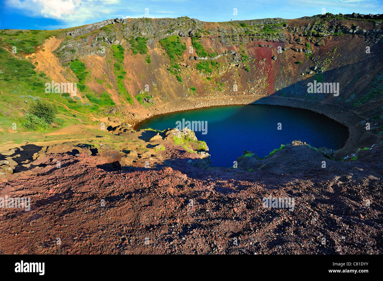 Kerid volcanic crater lake Grimsnes area of Iceland Unrecognizable people along caldera and climbing give senseStock Photo