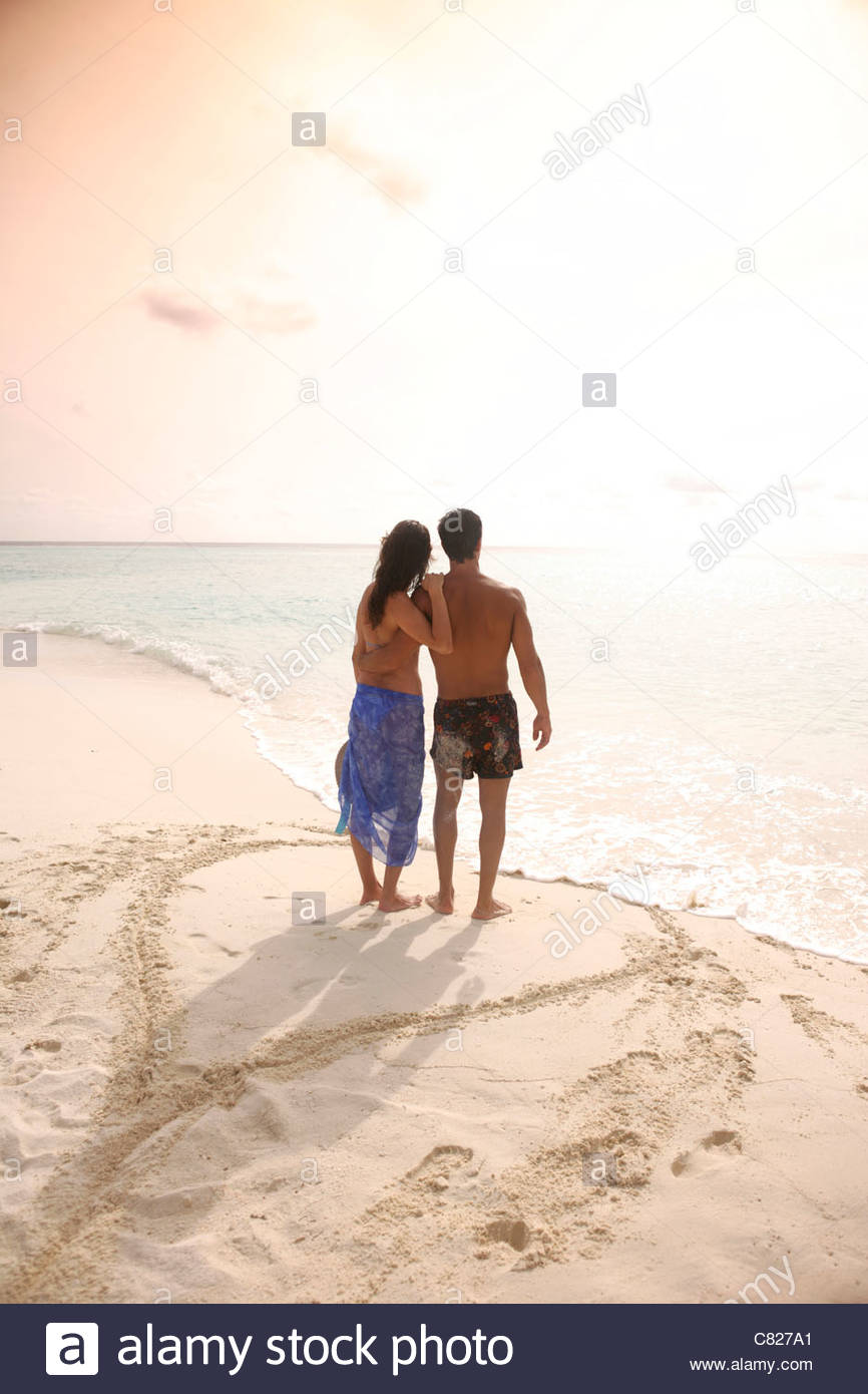 Couple at sea standing on heart drawn on sand - Stock Image