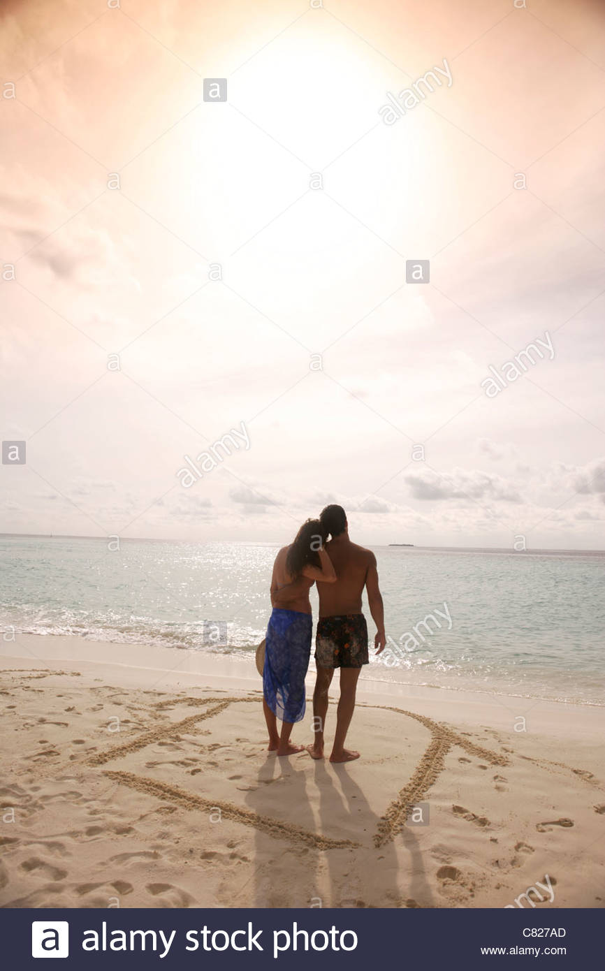 Couple at sea standing on house drawn on sand - Stock Image