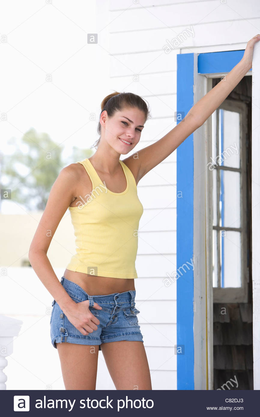 Woman leaning against doorframe - Stock Image