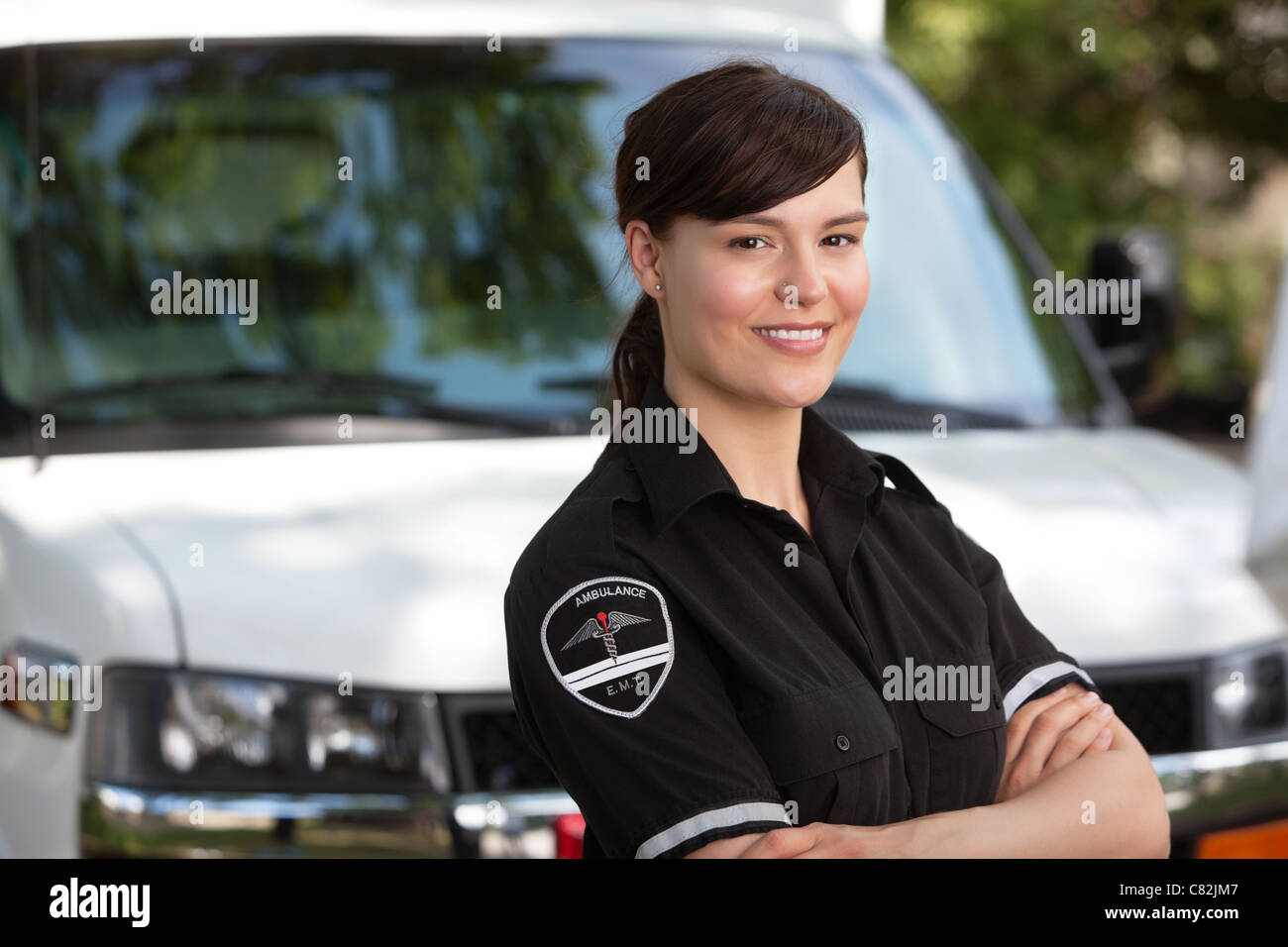 Portrait of a happy friendly female paramedic standing in front of ambulance - Stock Image