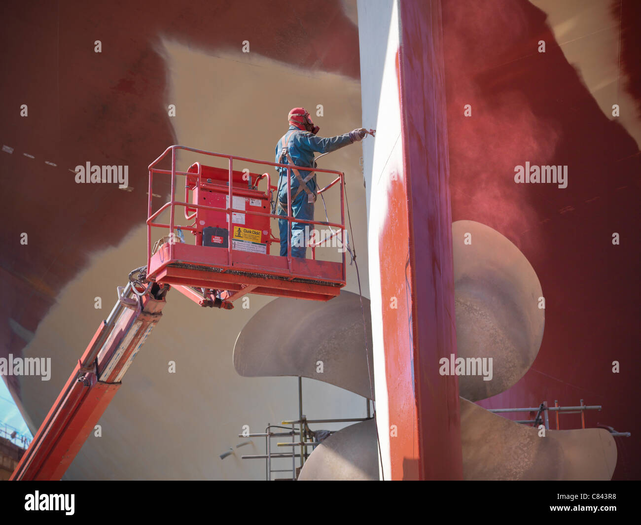 Worker painting ship's underside - Stock Image