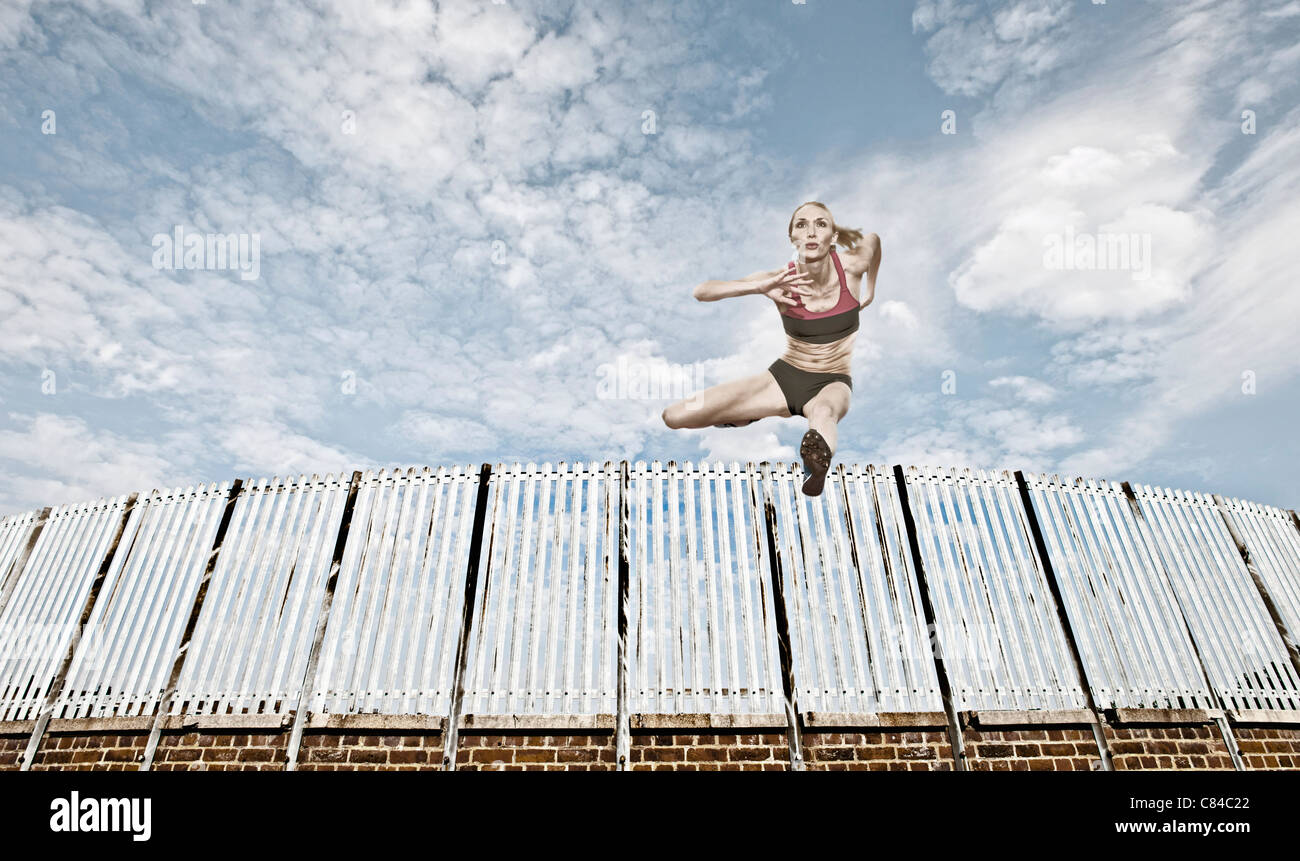 Athlete jumping over fence - Stock Image