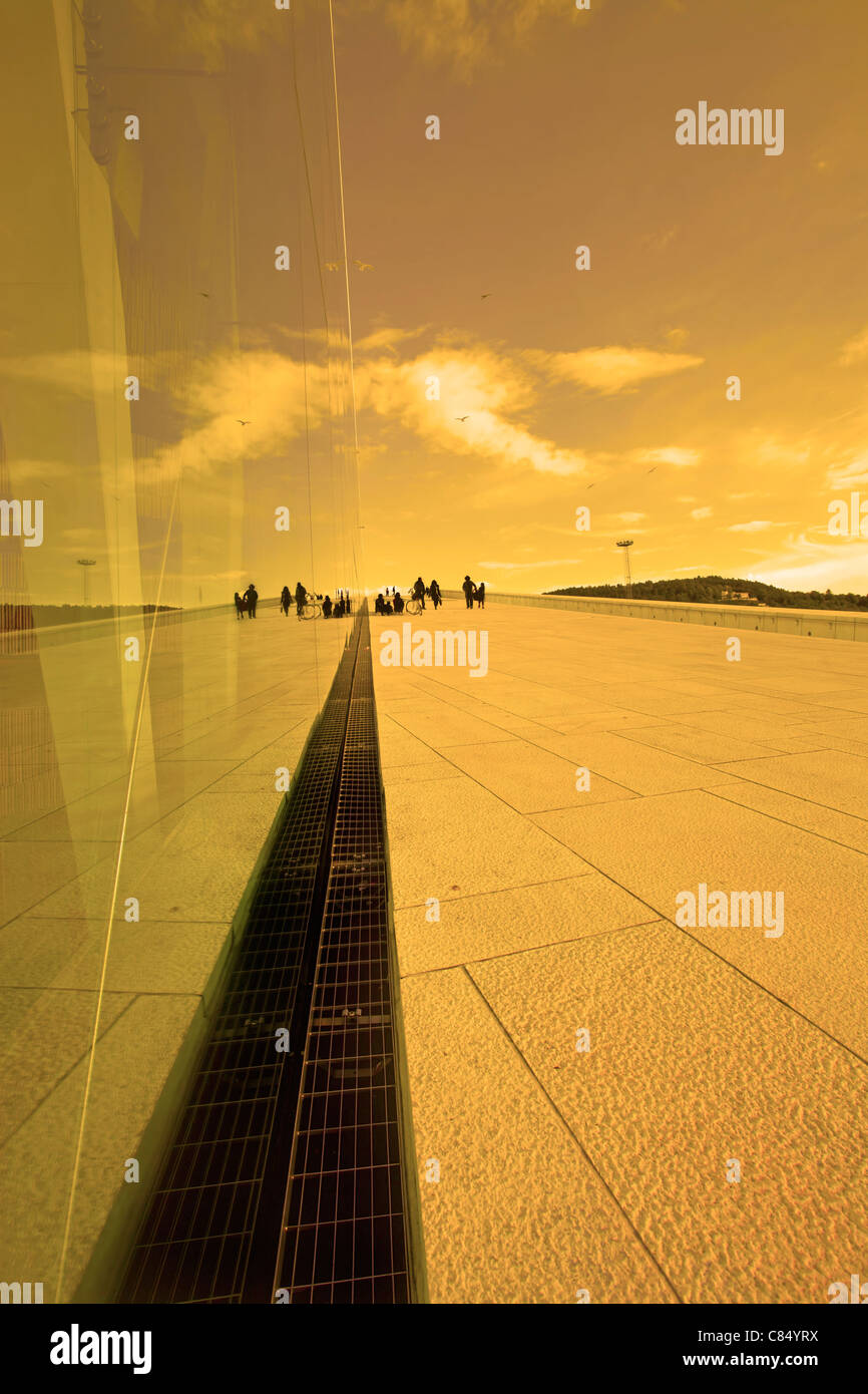 Reflection in a glass building at sunset - Stock Image