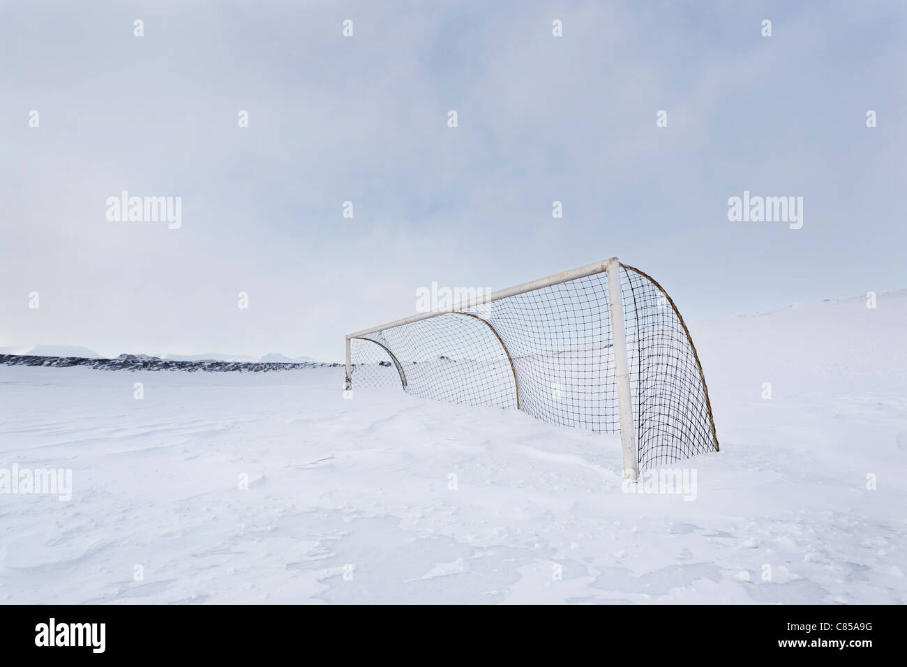 Hockey net in snow-covered field - Stock Image