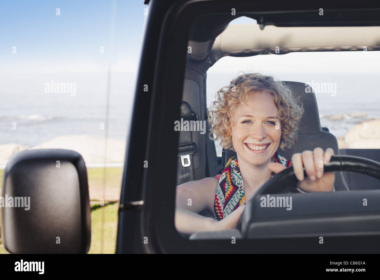 Smiling woman driving jeep - Stock Image