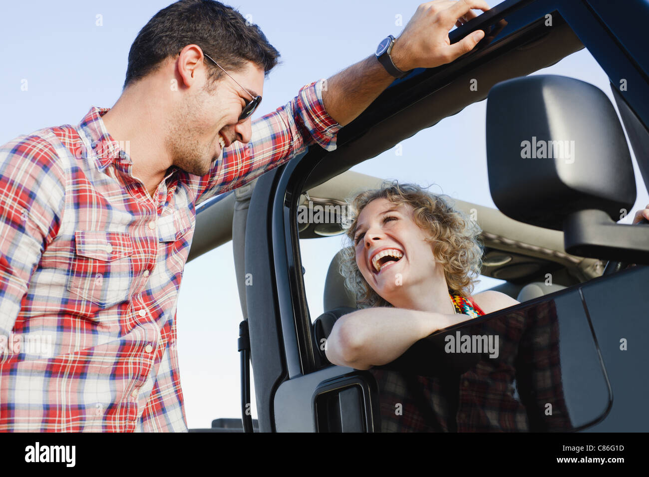Smiling couple talking near jeep - Stock Image