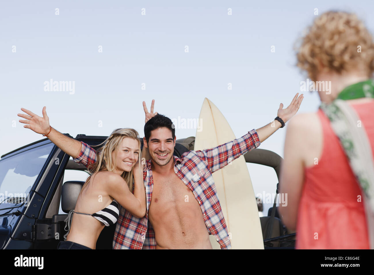 Girl taking picture of couple by jeep - Stock Image