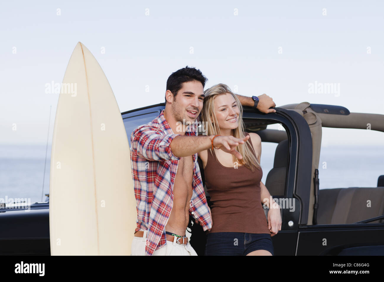 Smiling couple hugging by jeep - Stock Image