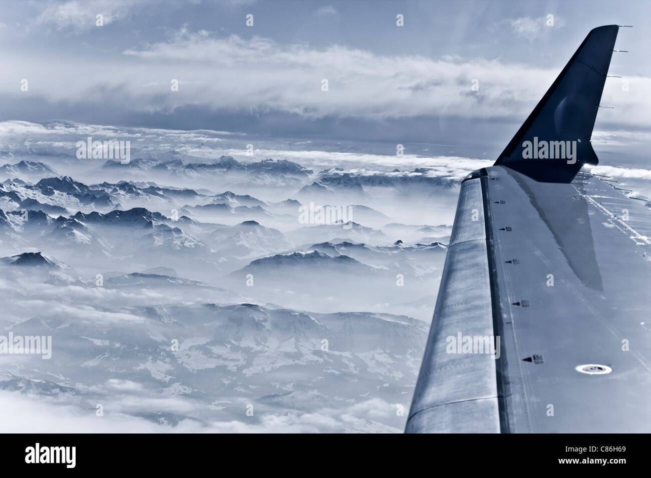 Airplane over snow covered mountains - Stock Image