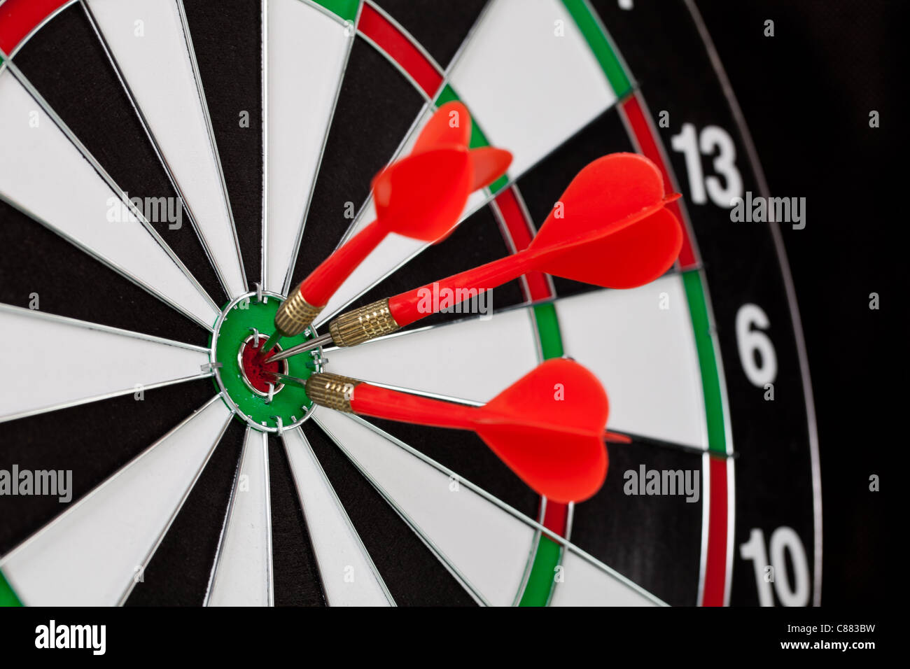 three darts hitting the bullseye on a dartboard stock photo