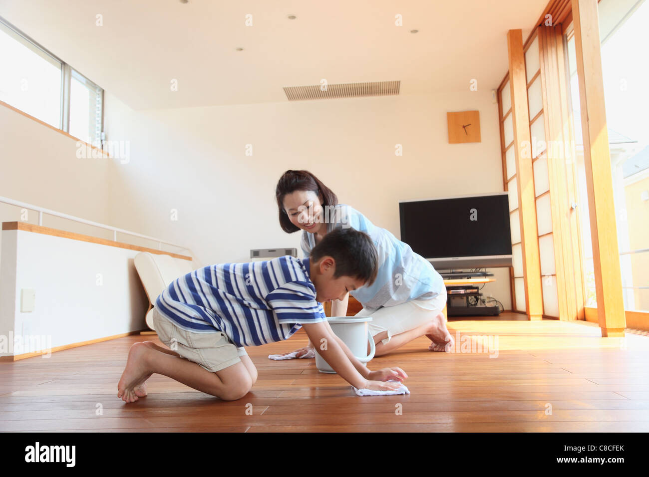 Mother and boy swabbing floor with dust cloth - Stock Image