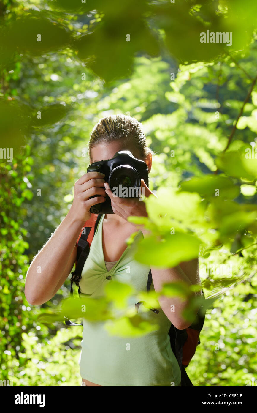young woman trekking among trees and taking pictures with dslr camera. Vertical shape, front view, waist up - Stock Image