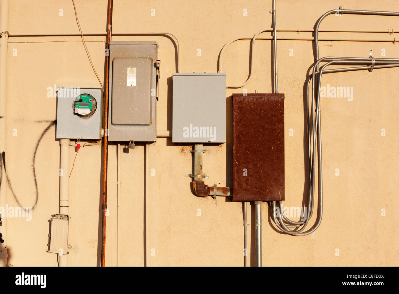 Electrical meter and fuse boxes on the side of a wall. - Stock Image