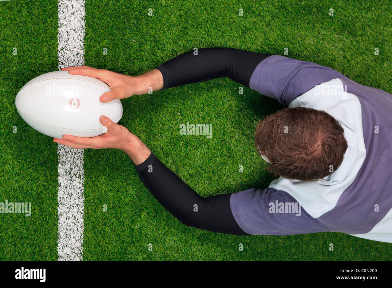 Overhead photo of a rugby player diving over the line to score a try with both hands holding the ball. - Stock Image