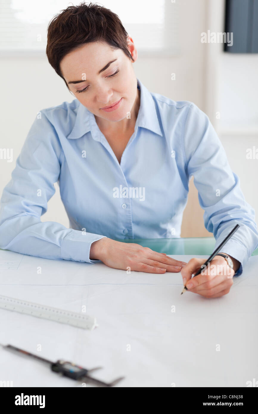 Woman working on an architectural plan - Stock Image